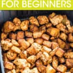 close up of cubed chicken and potatoes in an air fryer