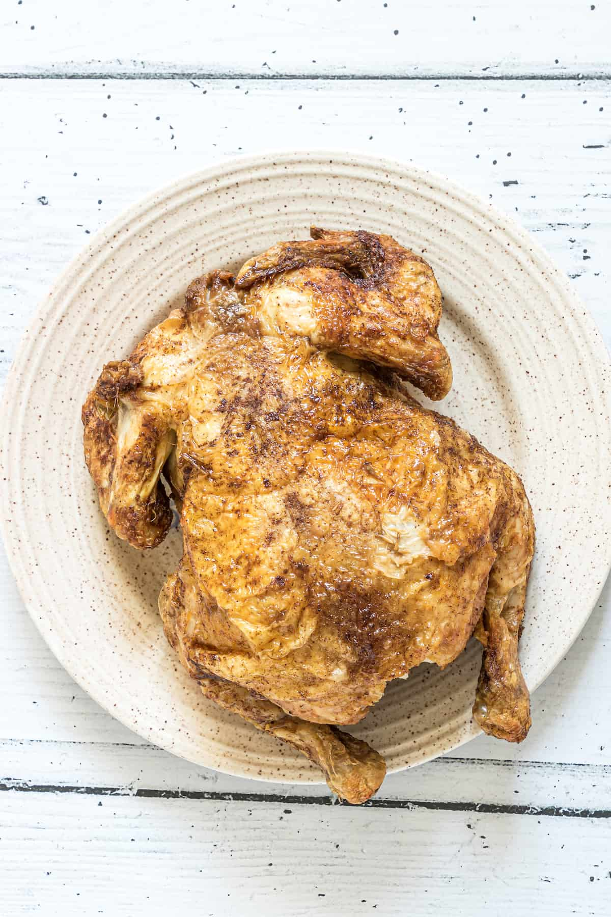 the finished air fryer whole chicken served on a white plate