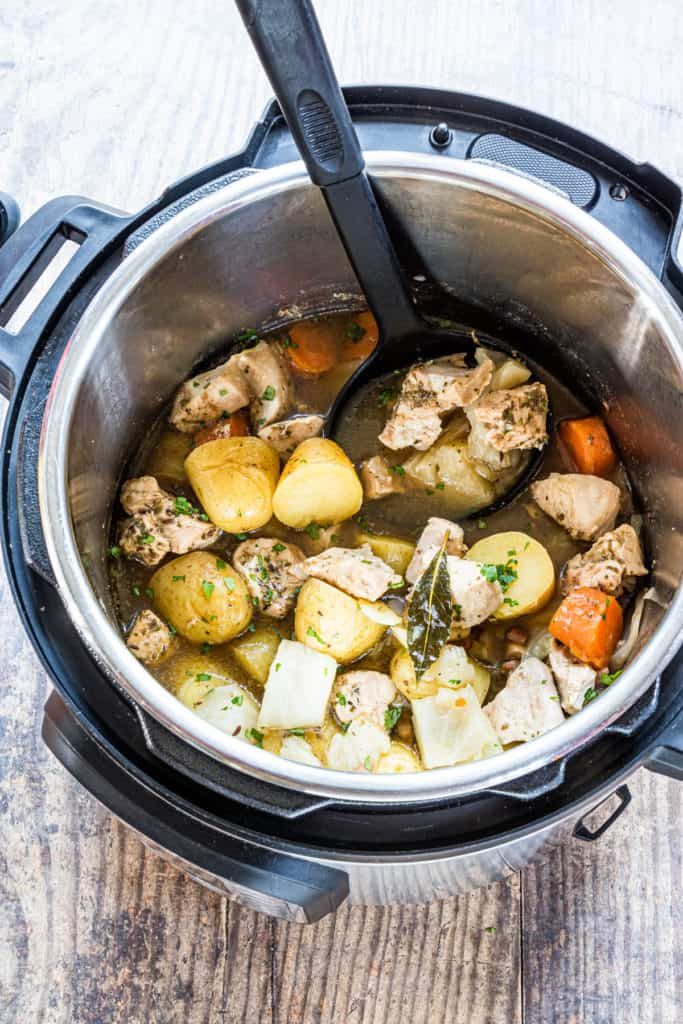 top down view of the completed irish chicken stew inside the instant pot with a ladle scooping out one serving