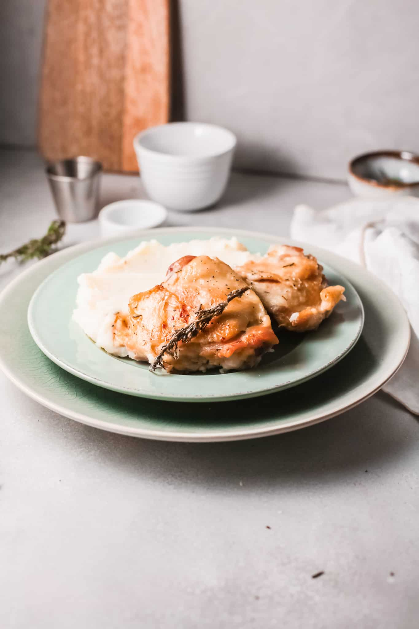 a serving of instant pot chicken thighs in rosemary cream sauce on a blue plate with mashed potatoes