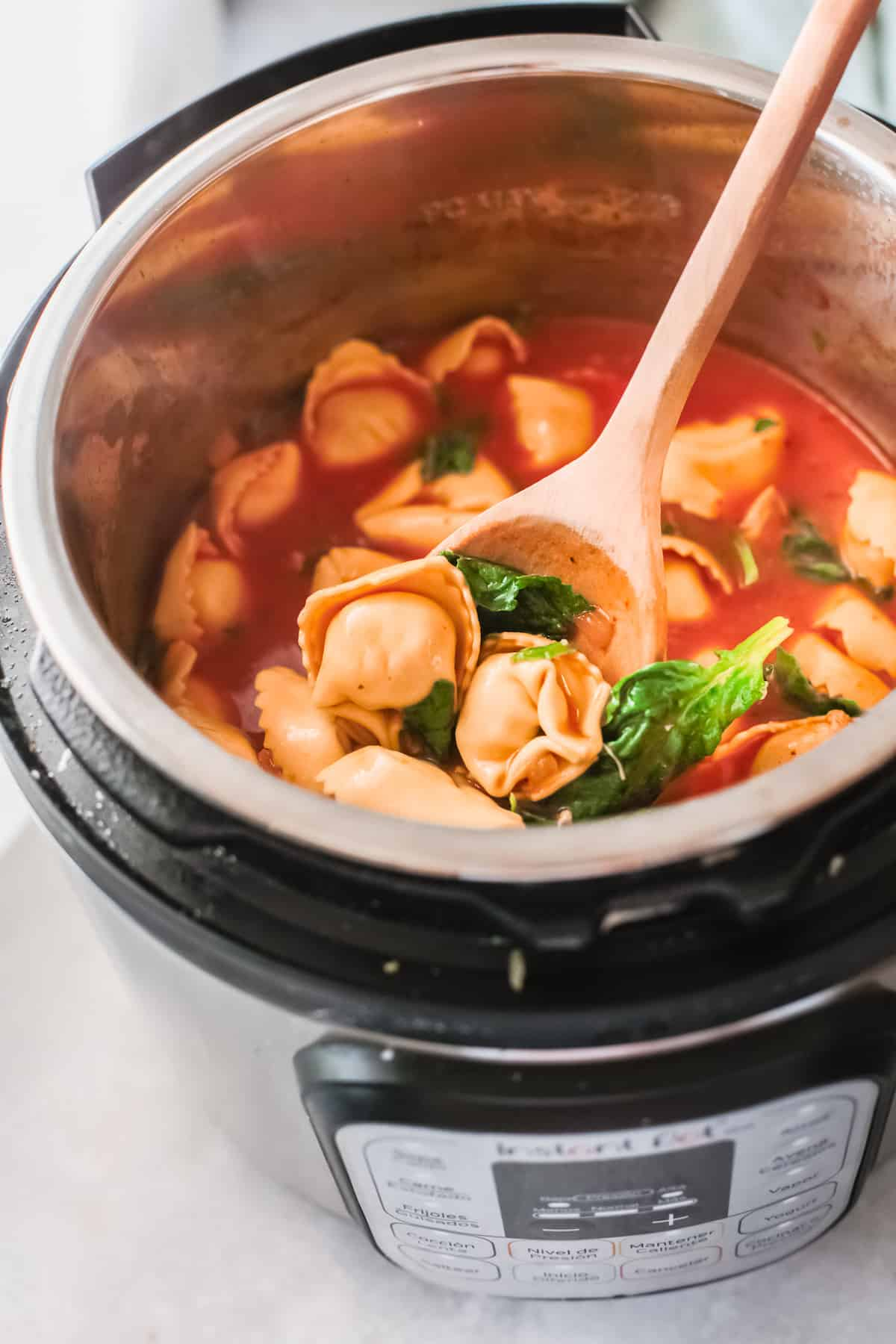 top down view of the finished instant pot chicken tortellini soup inside the instant pot
