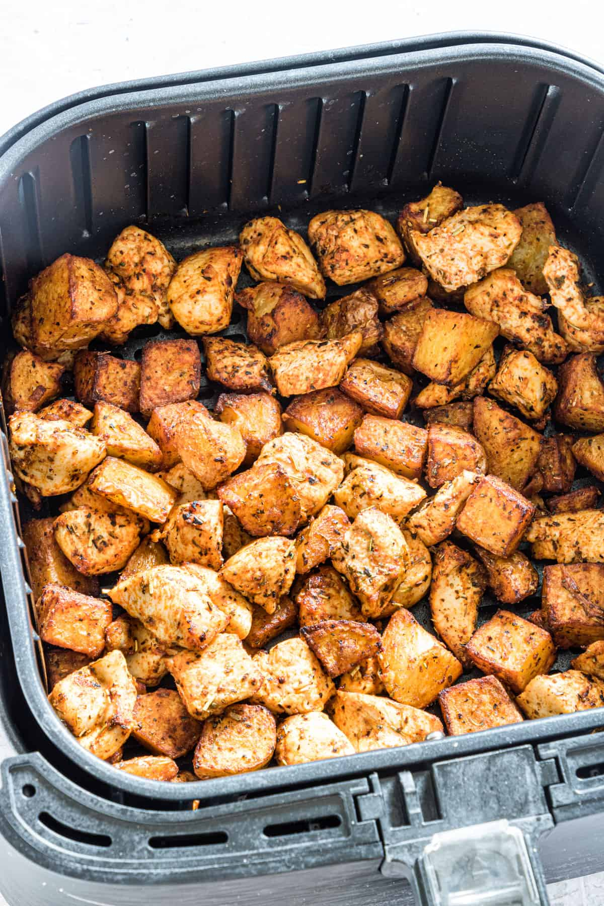 close up view of chicken and potatoes in the air fryer basket