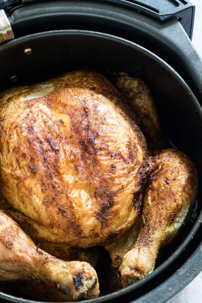 close up view of air fryer whole chicken inside the air fryer basket