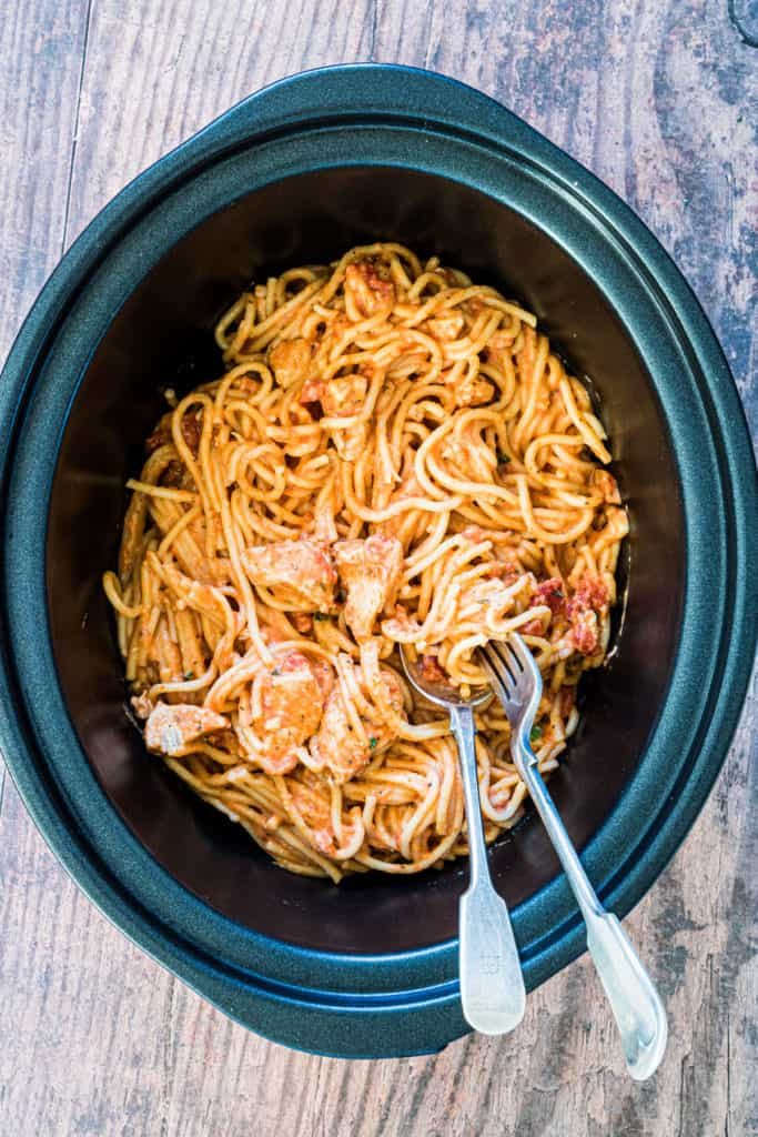 Slow Cooker Chicken Spaghetti in a crockpot with a fork and spoon