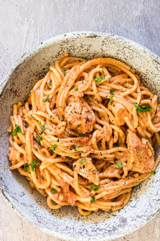 A hearty bowl of slow cooker spaghetti in a chicken and tomato sauce garnished with herbs