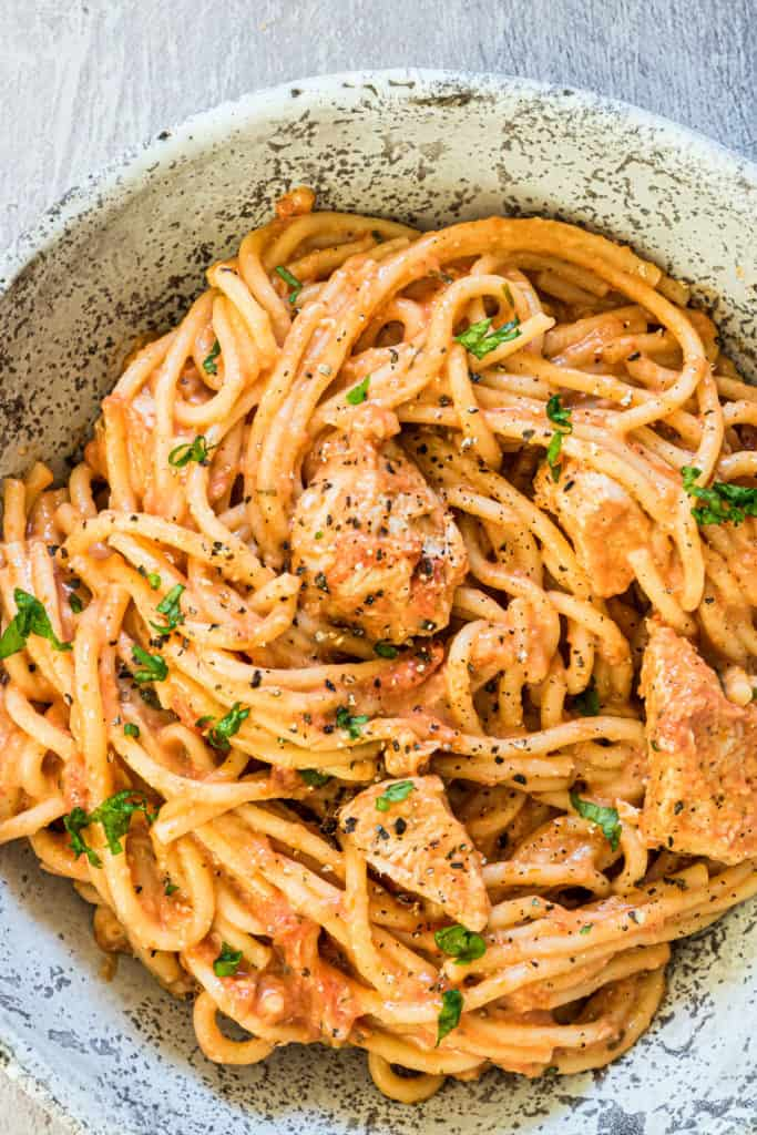 A bowl of chicken spaghetti with herbs and black pepper