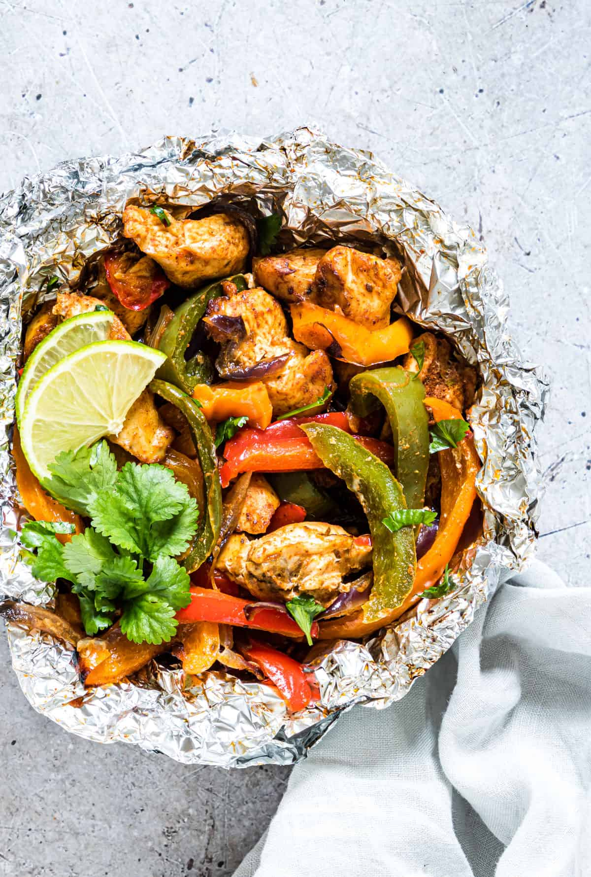 Easy cooked campfire chicken Fajitas in a foil packet with lime and cilantro garnish