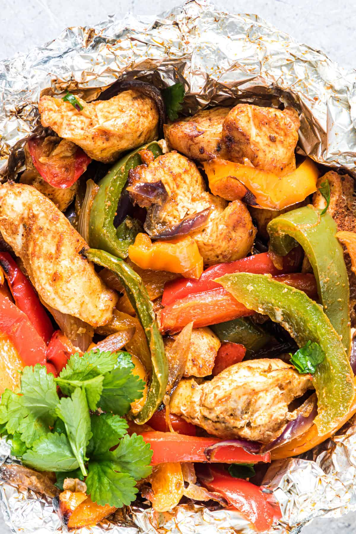 Close up of a cooked chicken fajita foil packet garnished with herbs