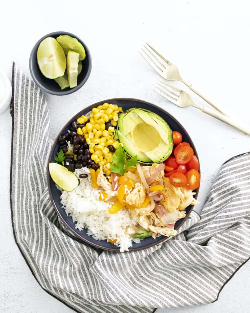 top down view of the finished chicken burrito served in a black bowl placed next to silverware and a striped cloth napkin