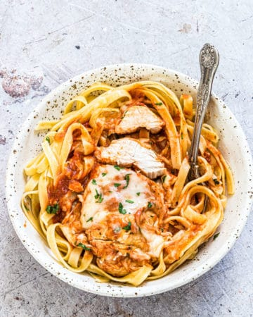 a bowl of instant pot chicken parmesan served on top of pasta