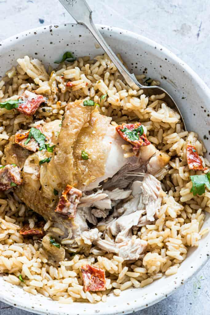 Cooked Creamy Sicilian Chicken Thighs served on a bowl of rice with a spoon