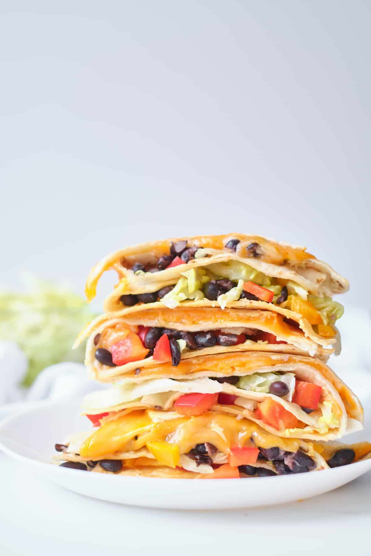 side view of the completed black bean quesadillas stacked and served on a plate