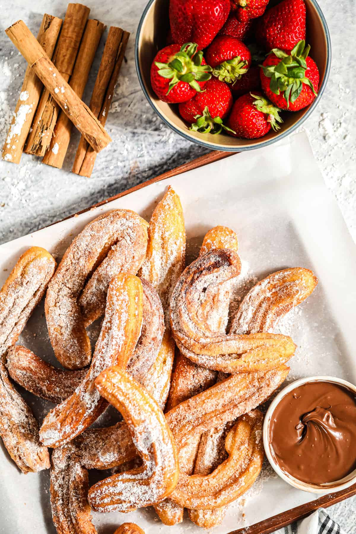 a tabletop of churros with strawberries