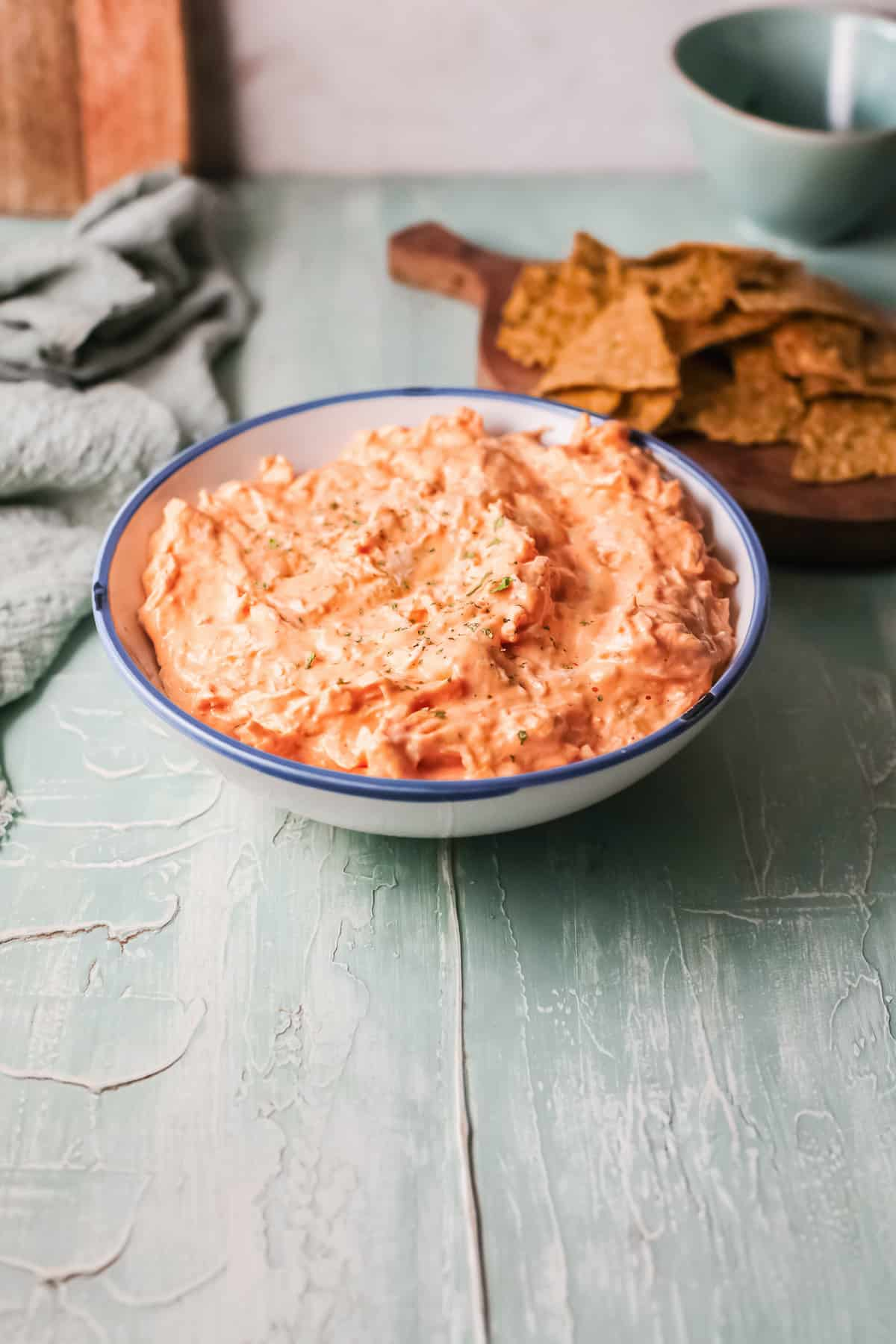 the completed crockpot buffalo chicken dip in a bowl on a tabletop with a serving of chips