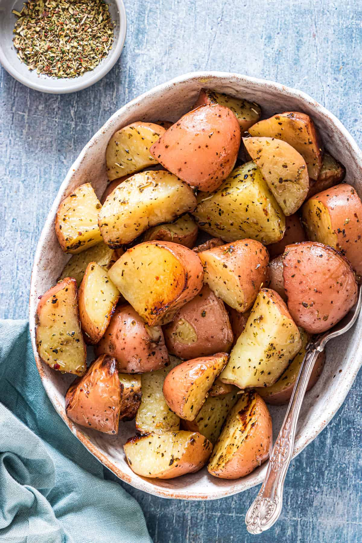 A bowl of cooked red potatoes with some seasoning on the saide