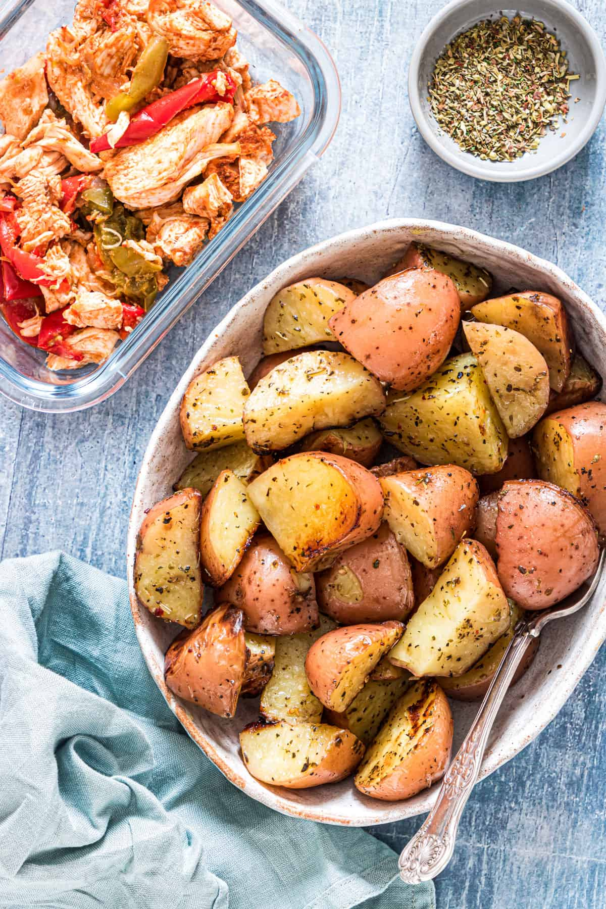 a table with a bowl of grilled potatoes, seasoning and chicken