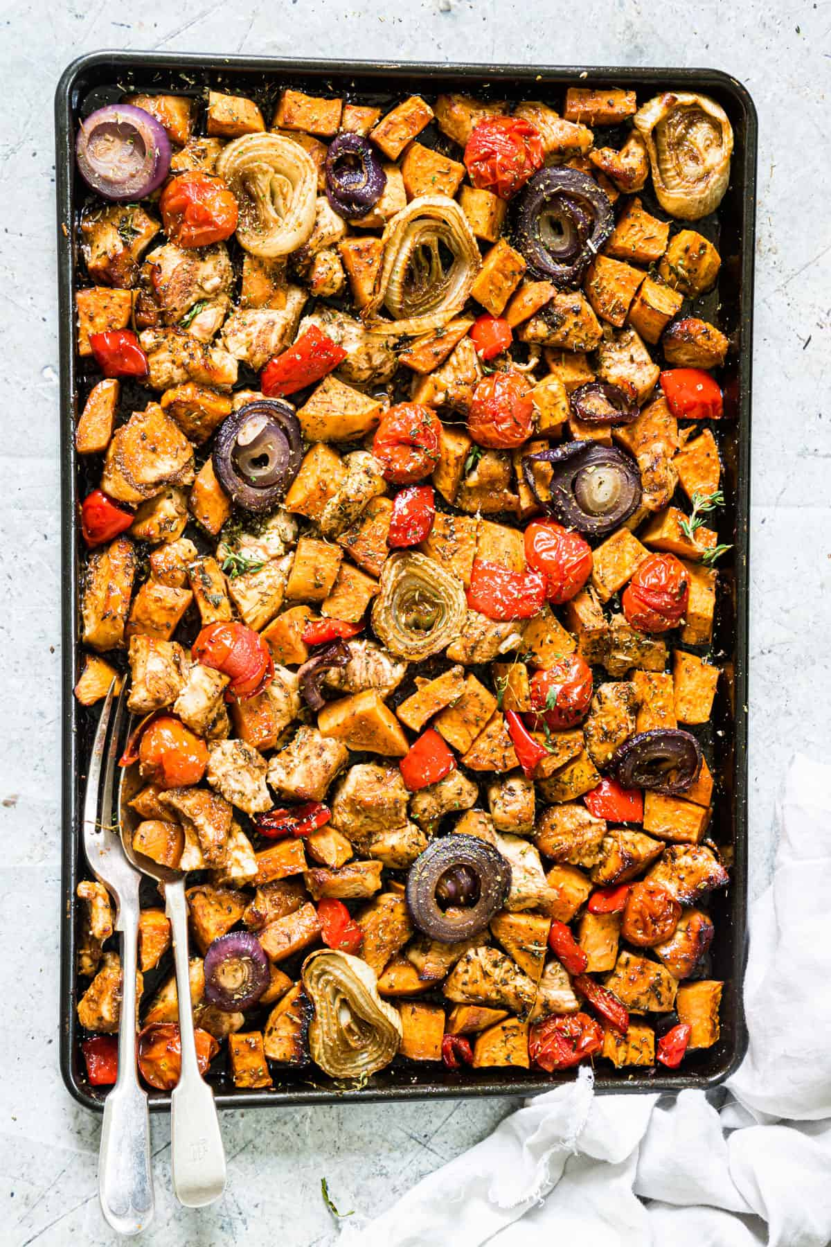 top down view of a sheet pan with chicken and veggies