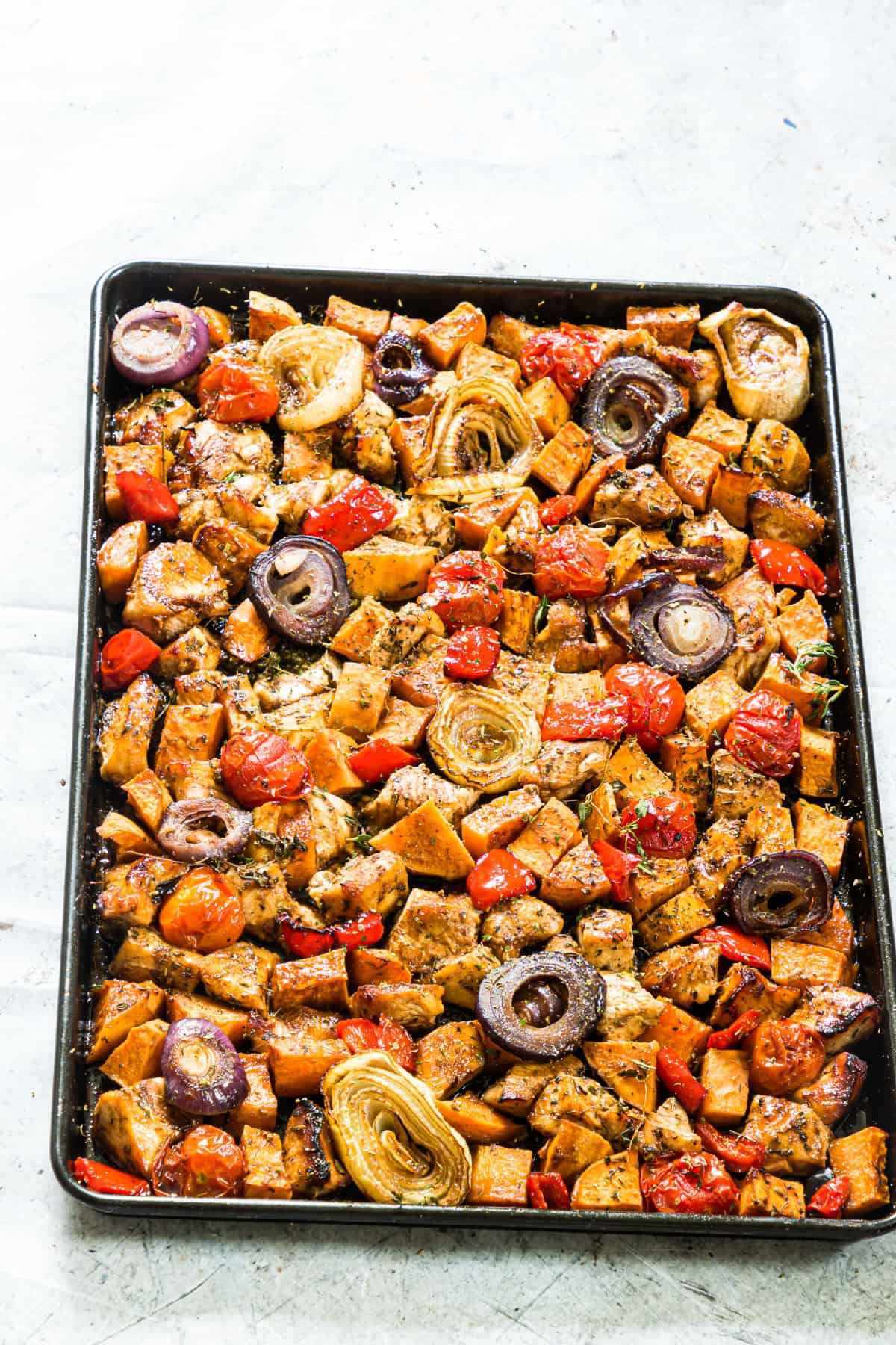 the sheet pan filled with cooked chicken and veggies