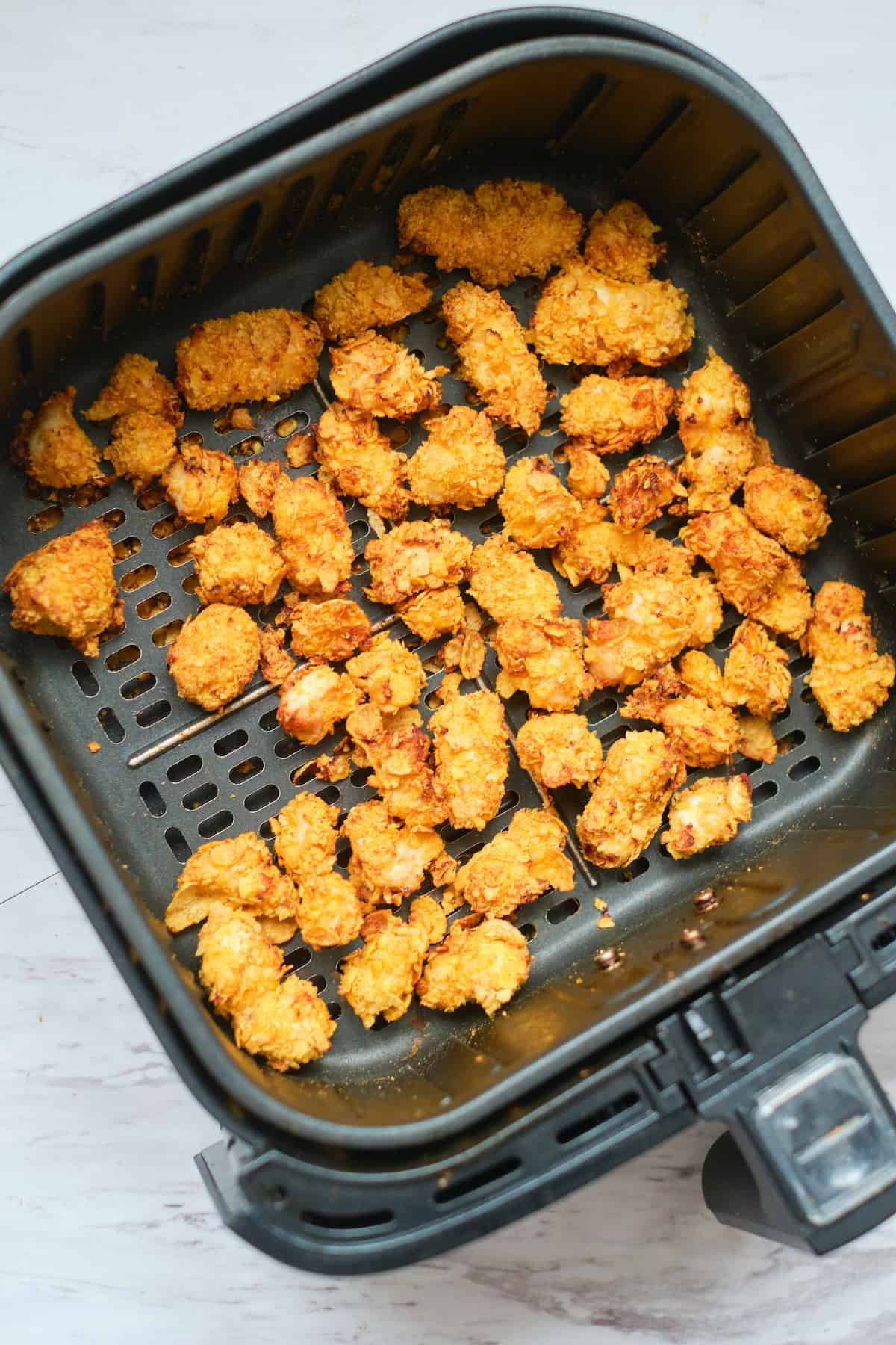 top down view of the cooked popcorn chicken inside the air fryer basket