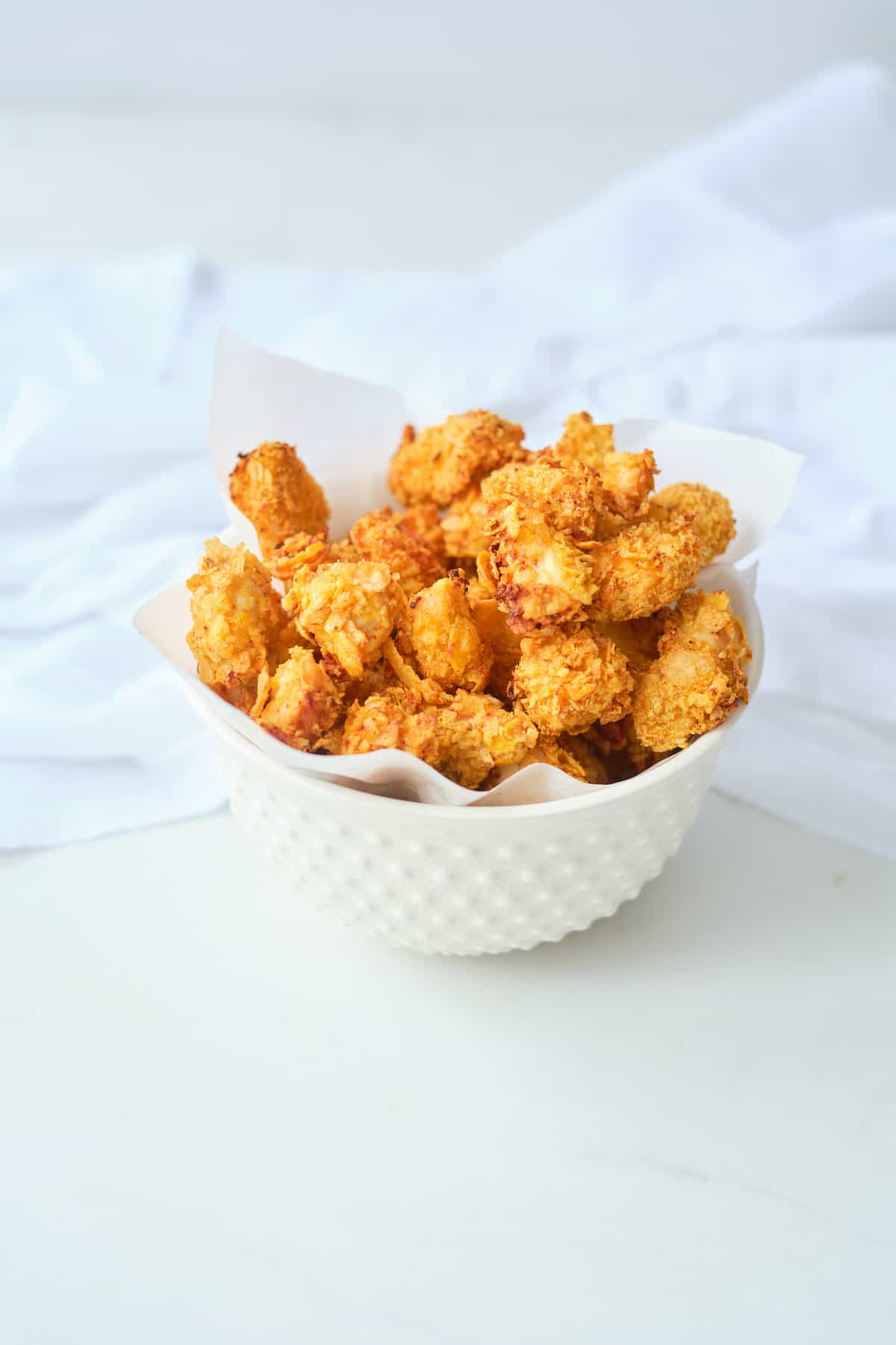 a white bowl filled with air fryer popcorn chicken