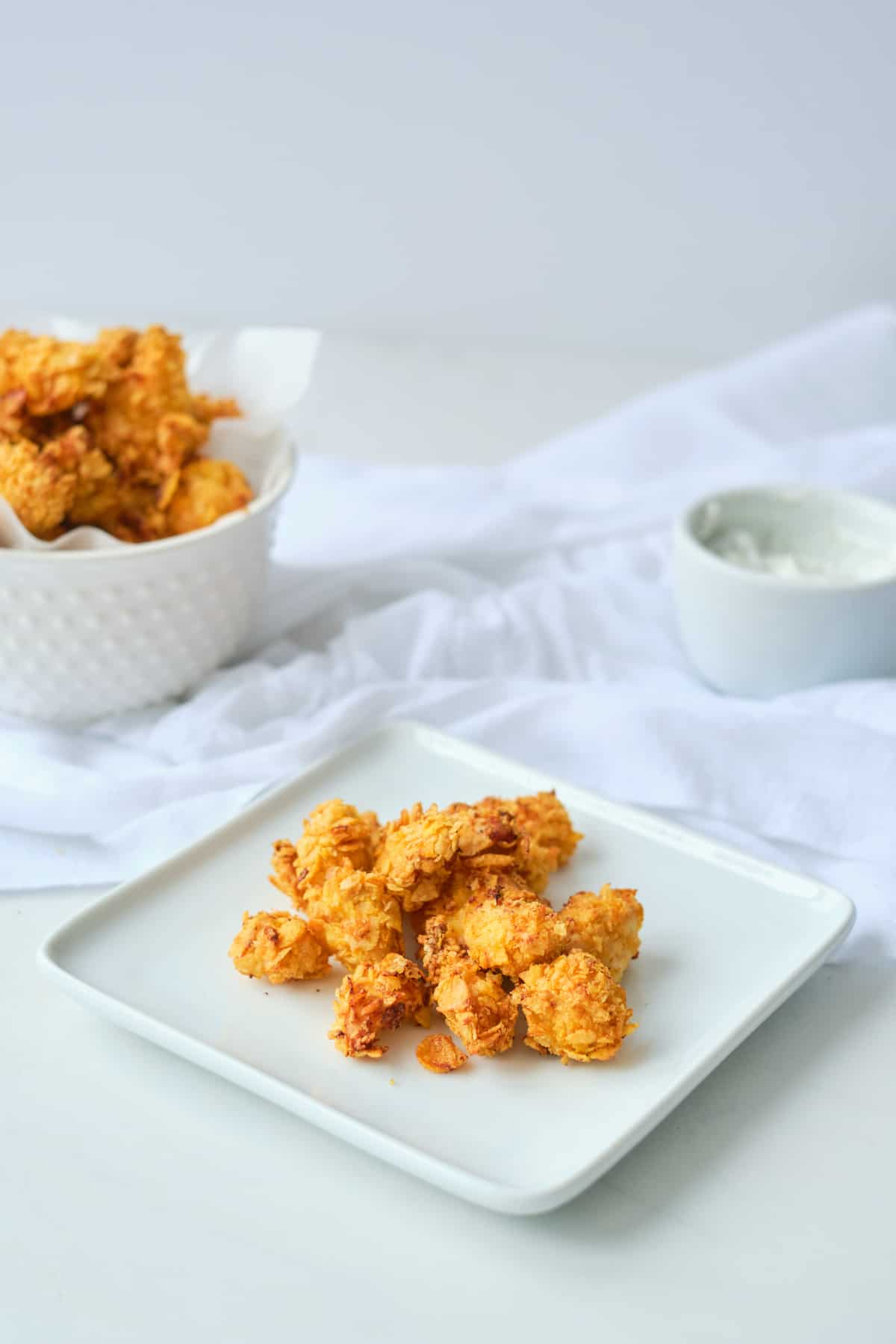 a plate of air fryer popcorn chicken set in front of a dipping sauce cup and a bowl of the finished popcorn chicken