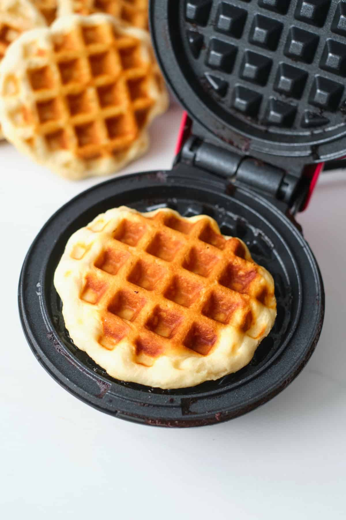 one of the cooked biscuit waffles inside the waffle maker