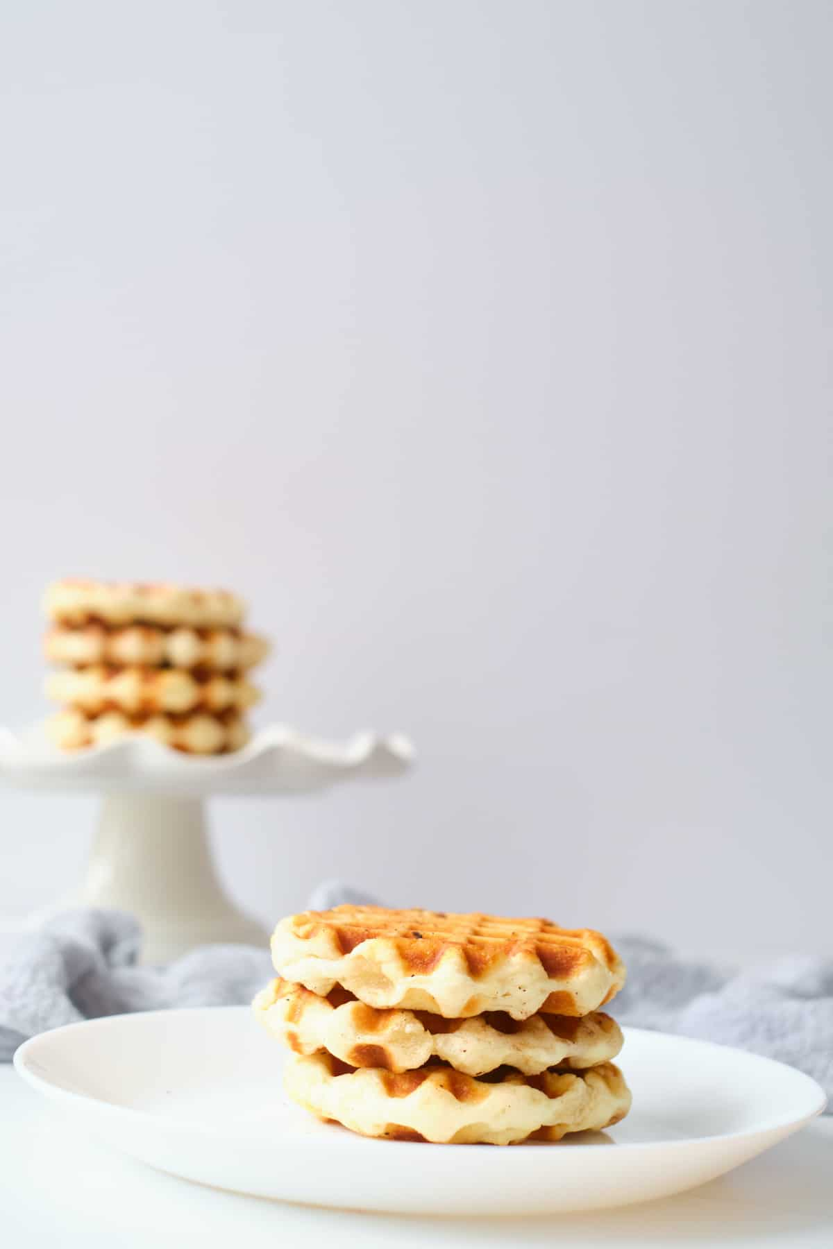 3 of the finished biscuit waffles on a white plate with another stack behind them