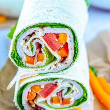 the completed chicken wrap with bacon and ranch served on parchment paper with carrot sticks