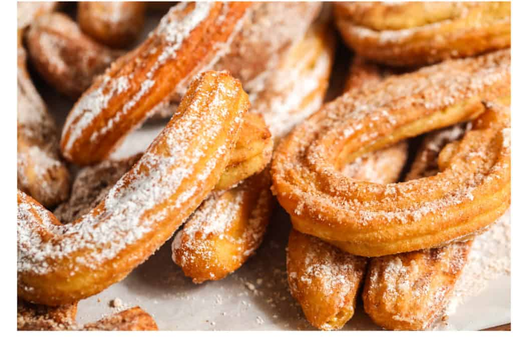 close up of churros with powdered sugar on a plate