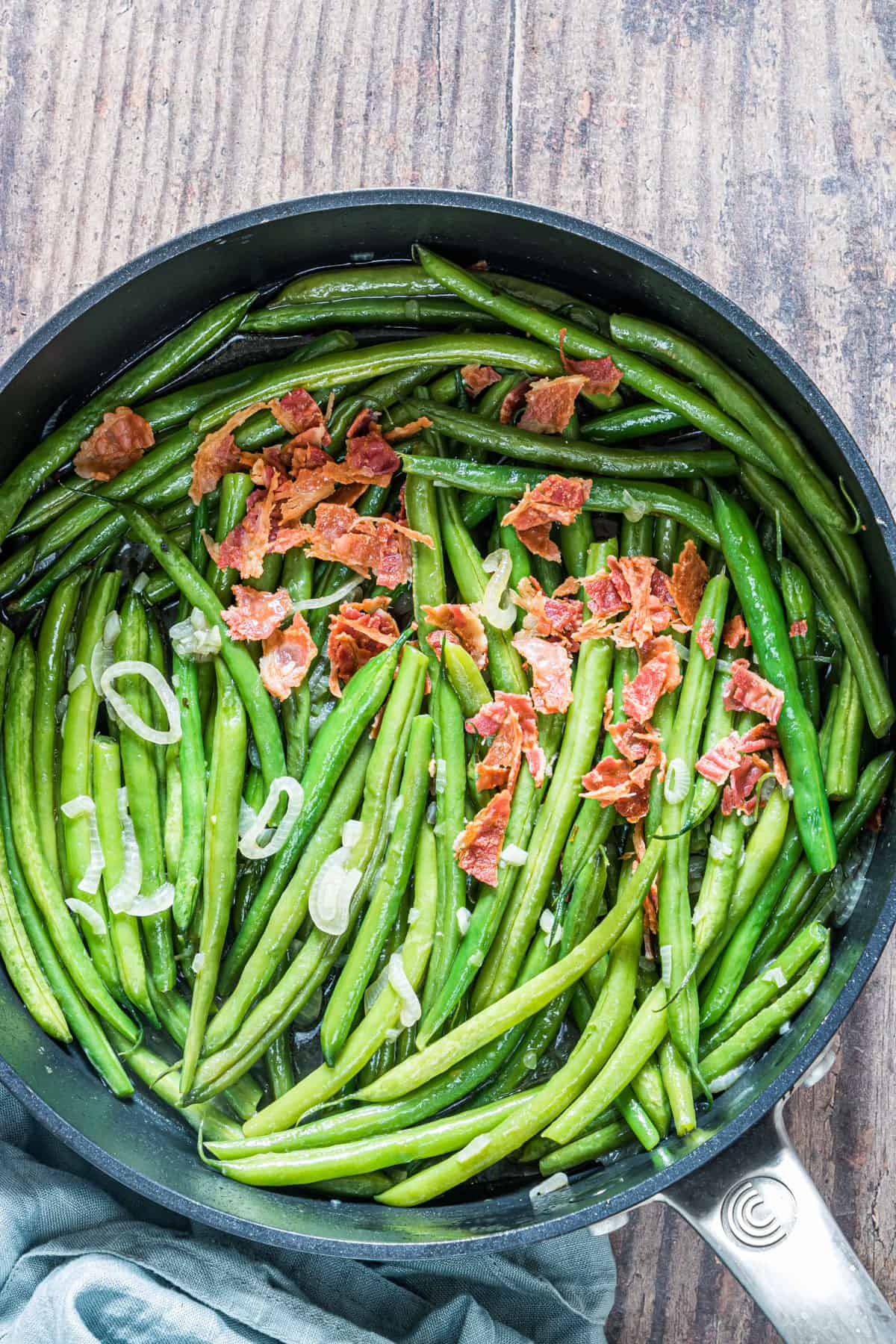 smothered green beans in a skillet set on a cloth napkin