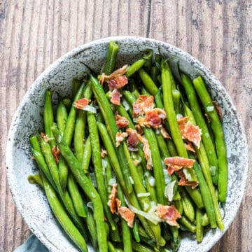 the finished green beans with bacon on a ceramic serving bowl
