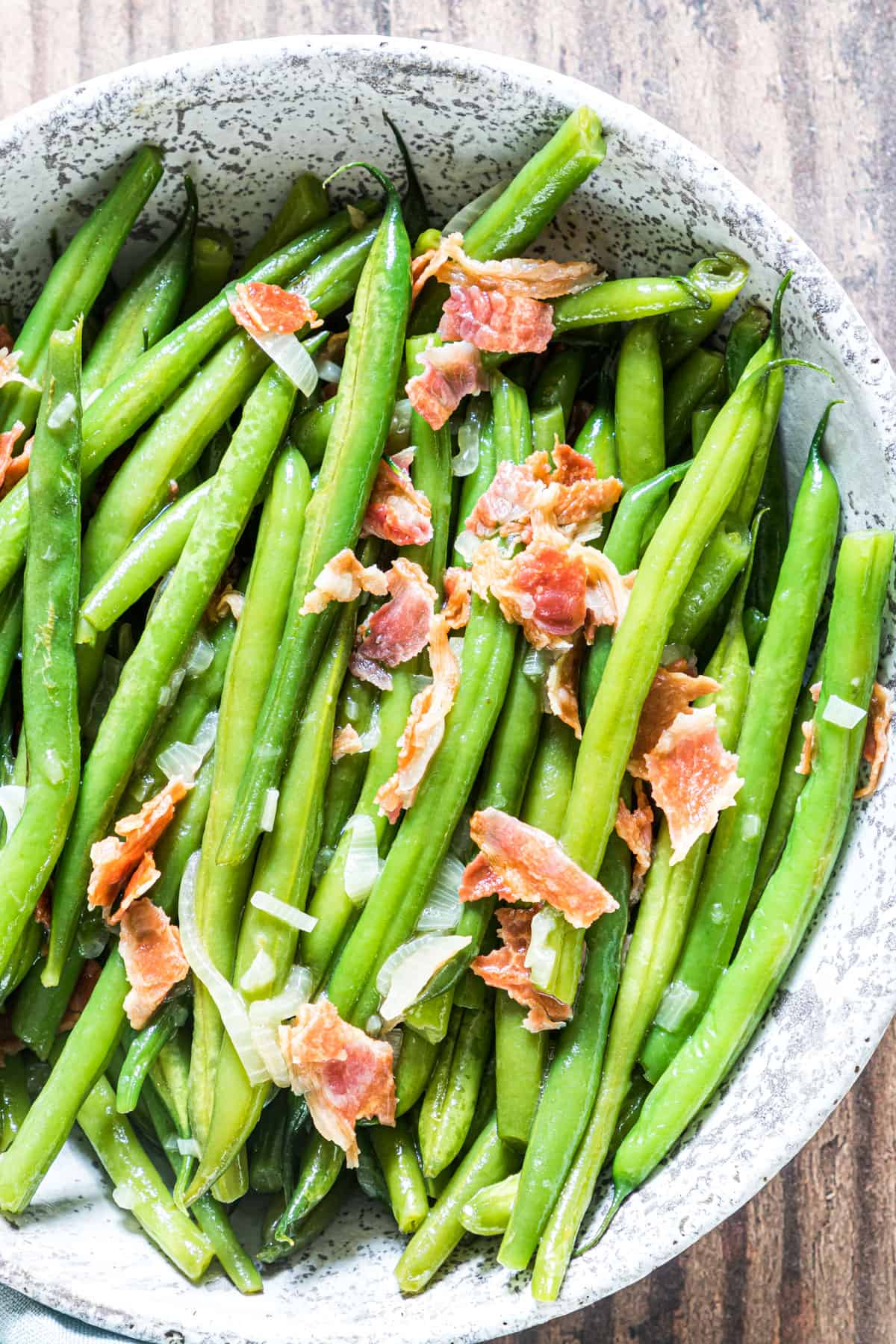 the smothered green beans with bacon in a ceramic serving dish