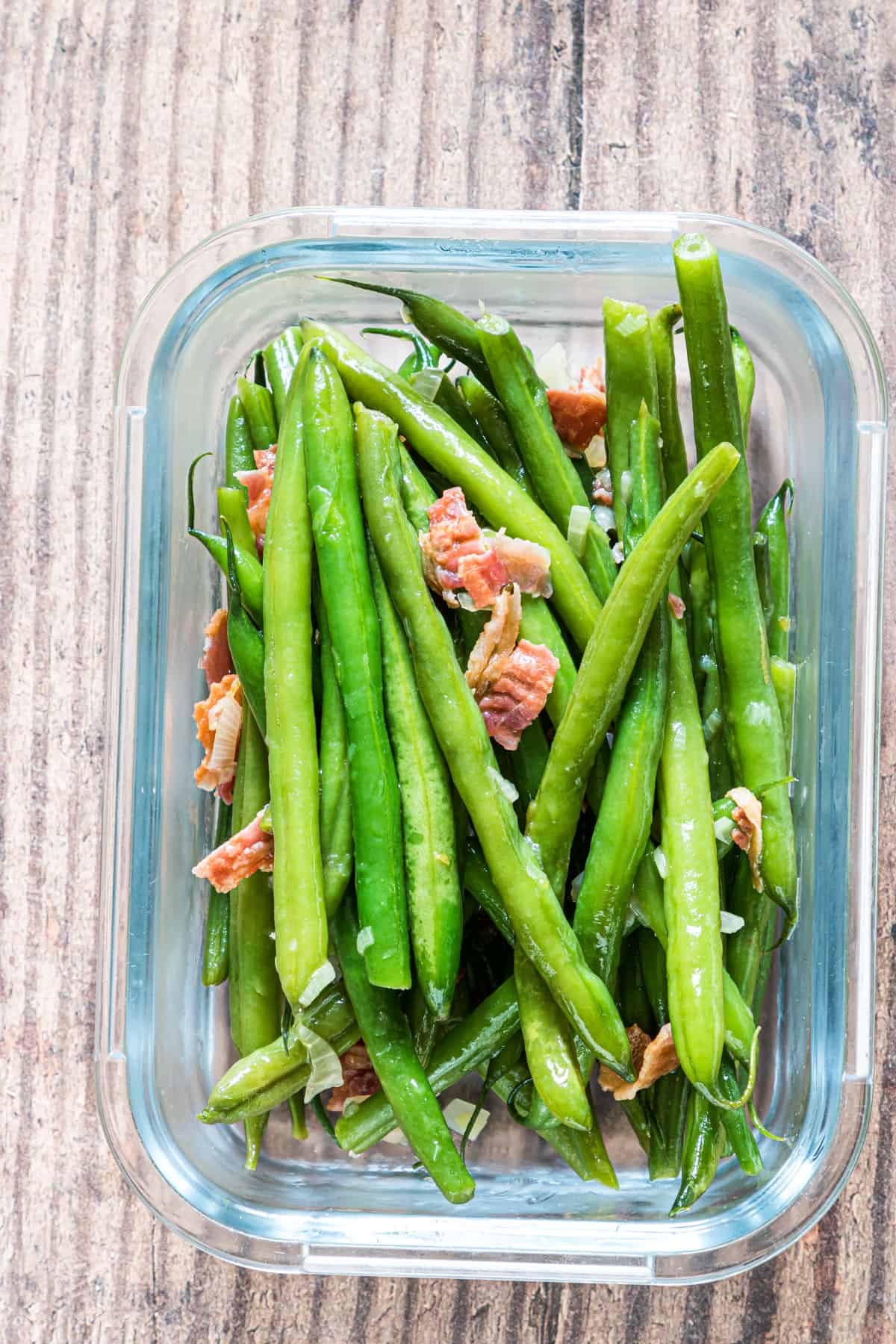 green beans with bacon inside a glass food storage container
