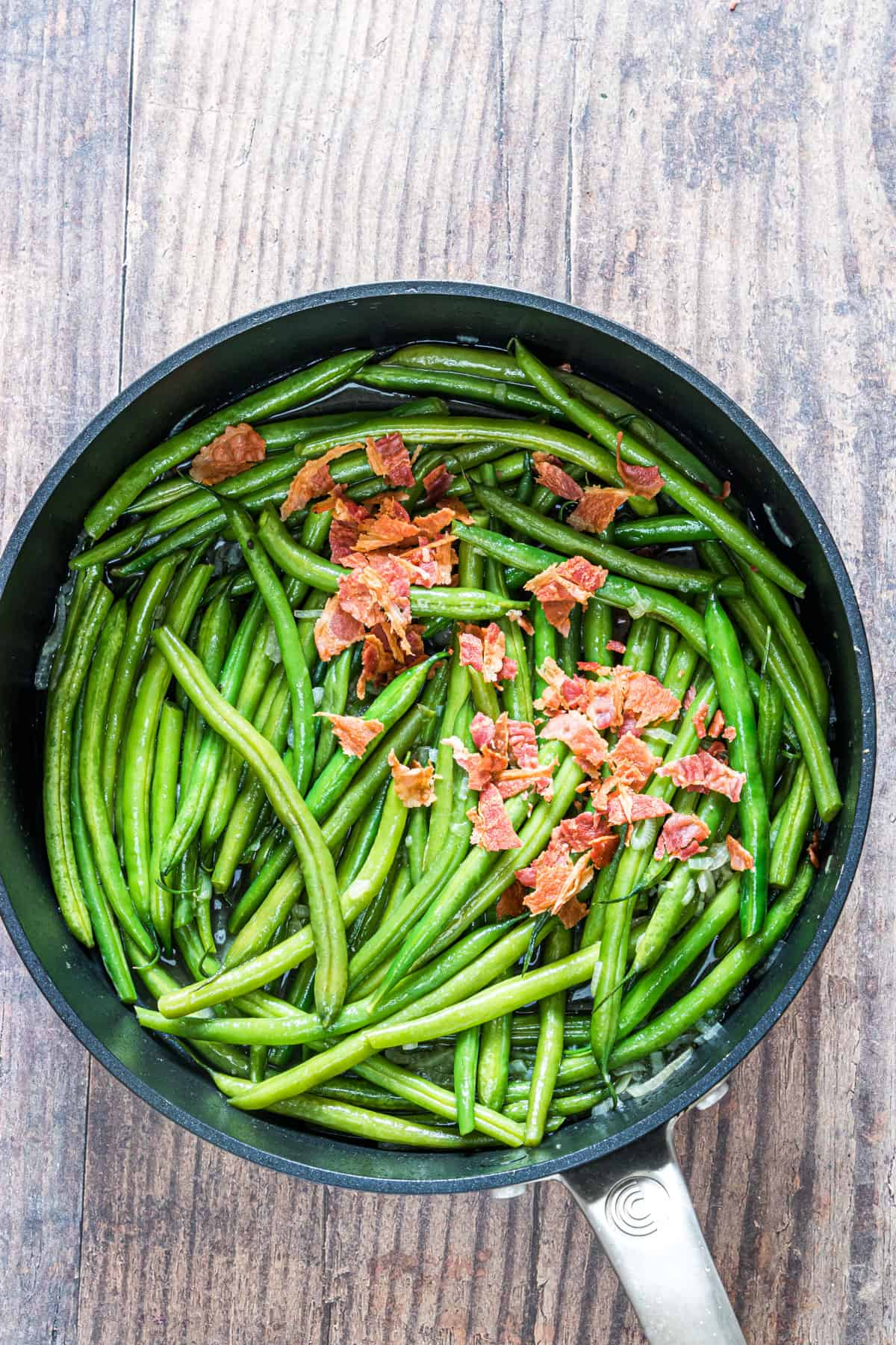 top down view of the cooked green beans with bacon inside a skillet