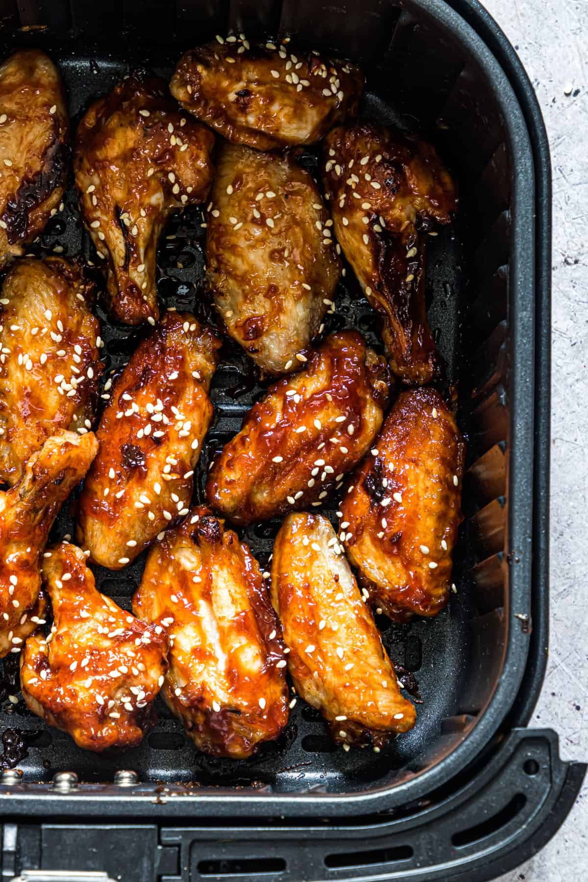 Close up of stick air fryer chicken wings in the air fryer basket