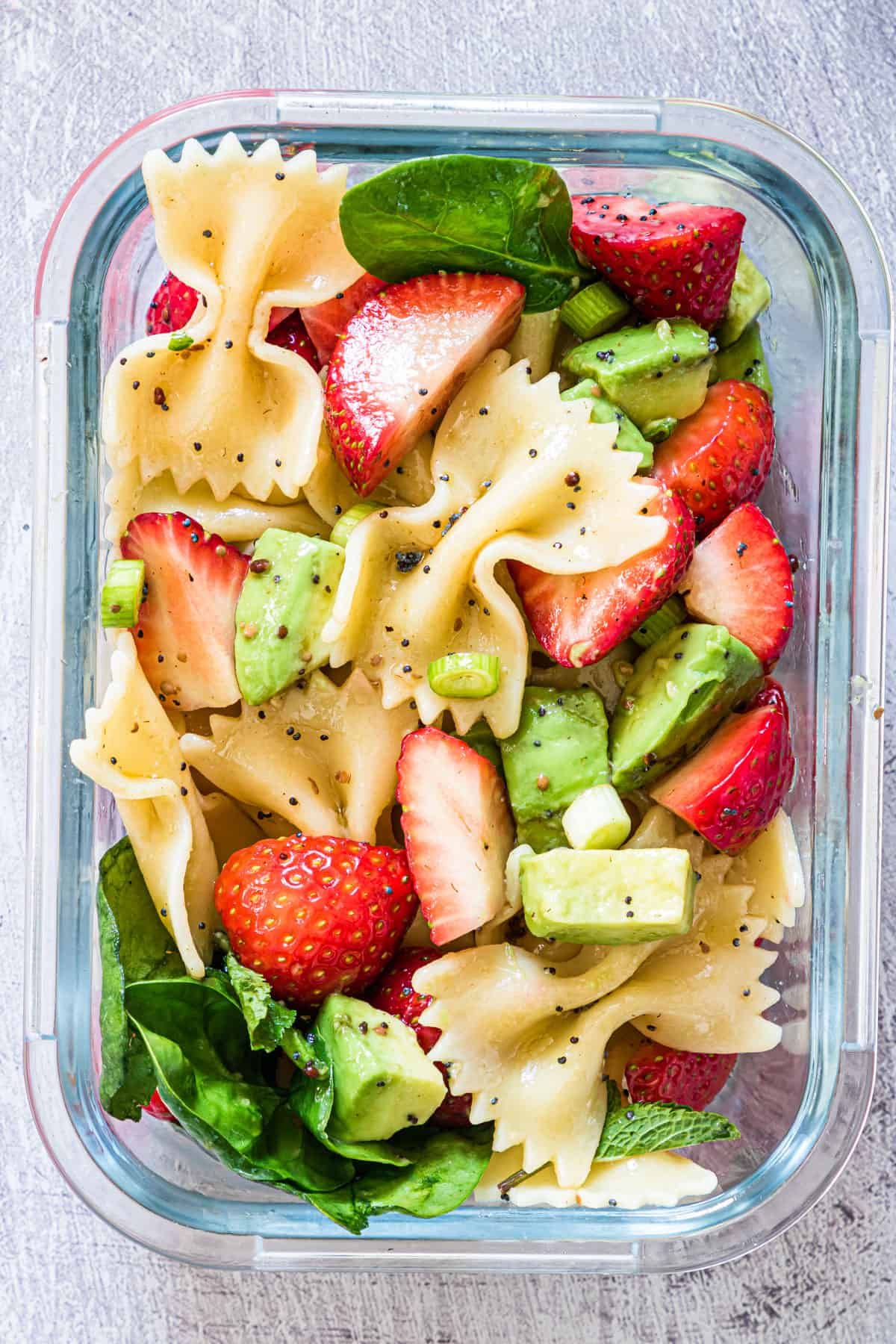 one serving of strawberry avocado pasta salad inside a glass food storage container