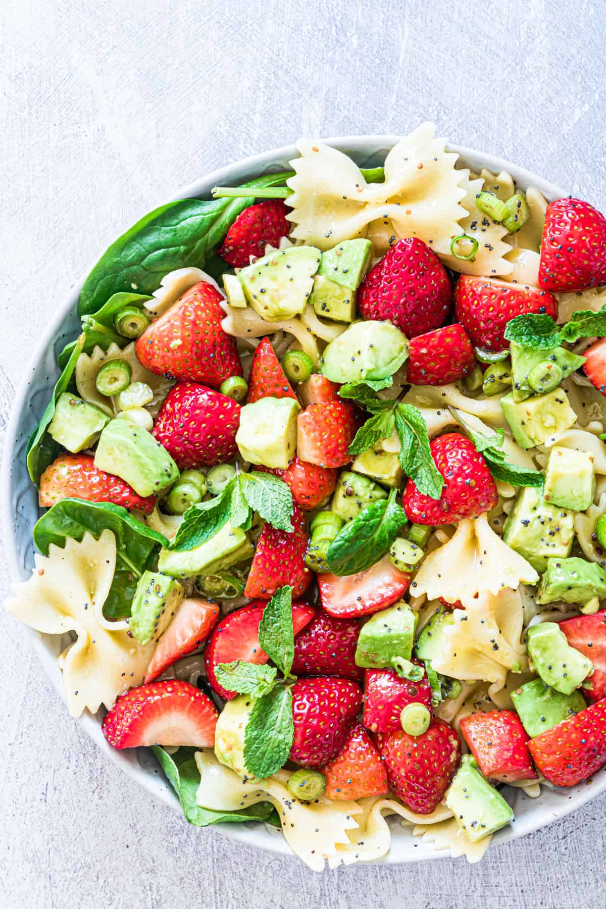 a bowl filled with the finished strawberry avocado pasta salad