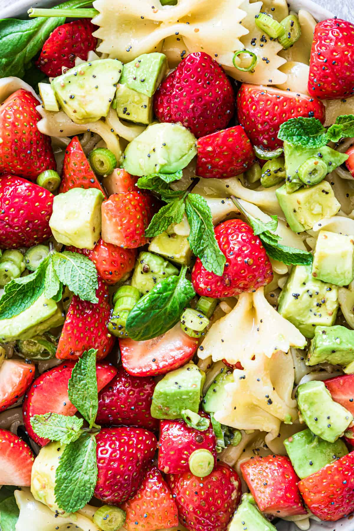 close up view of the ingredients used to make strawberry avocado pasta salad