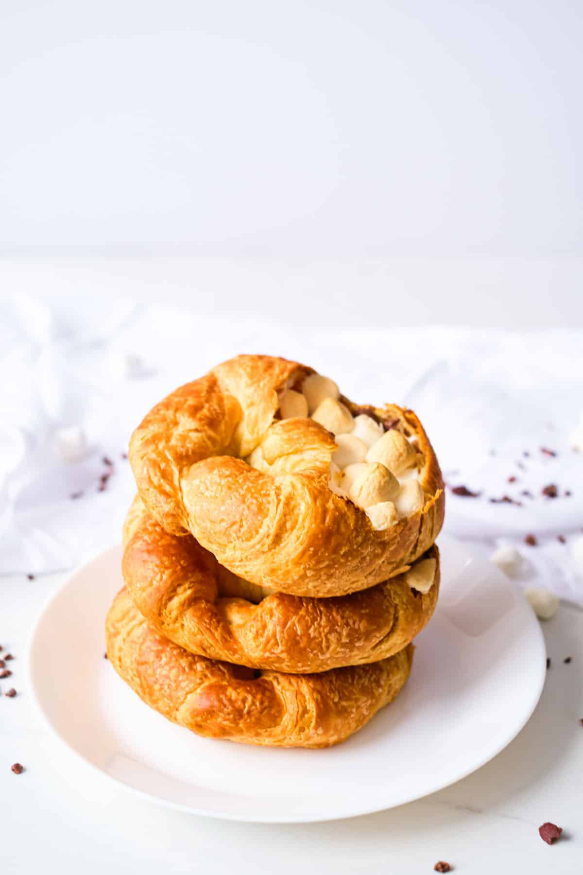 three completed stuffed croissant breakfast boats stacked on a white plate