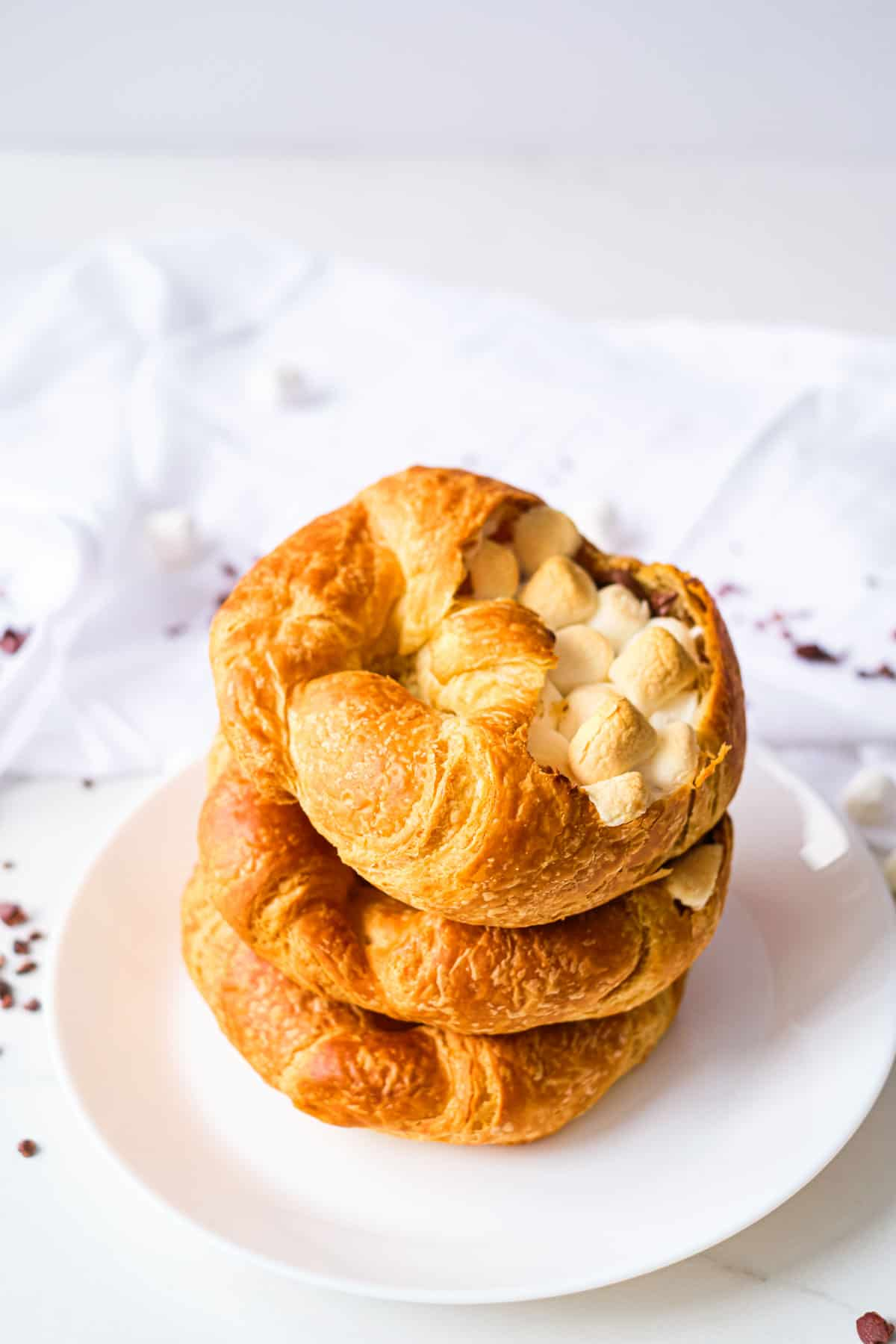 three stuffed croissants stacked vertically on a white plate