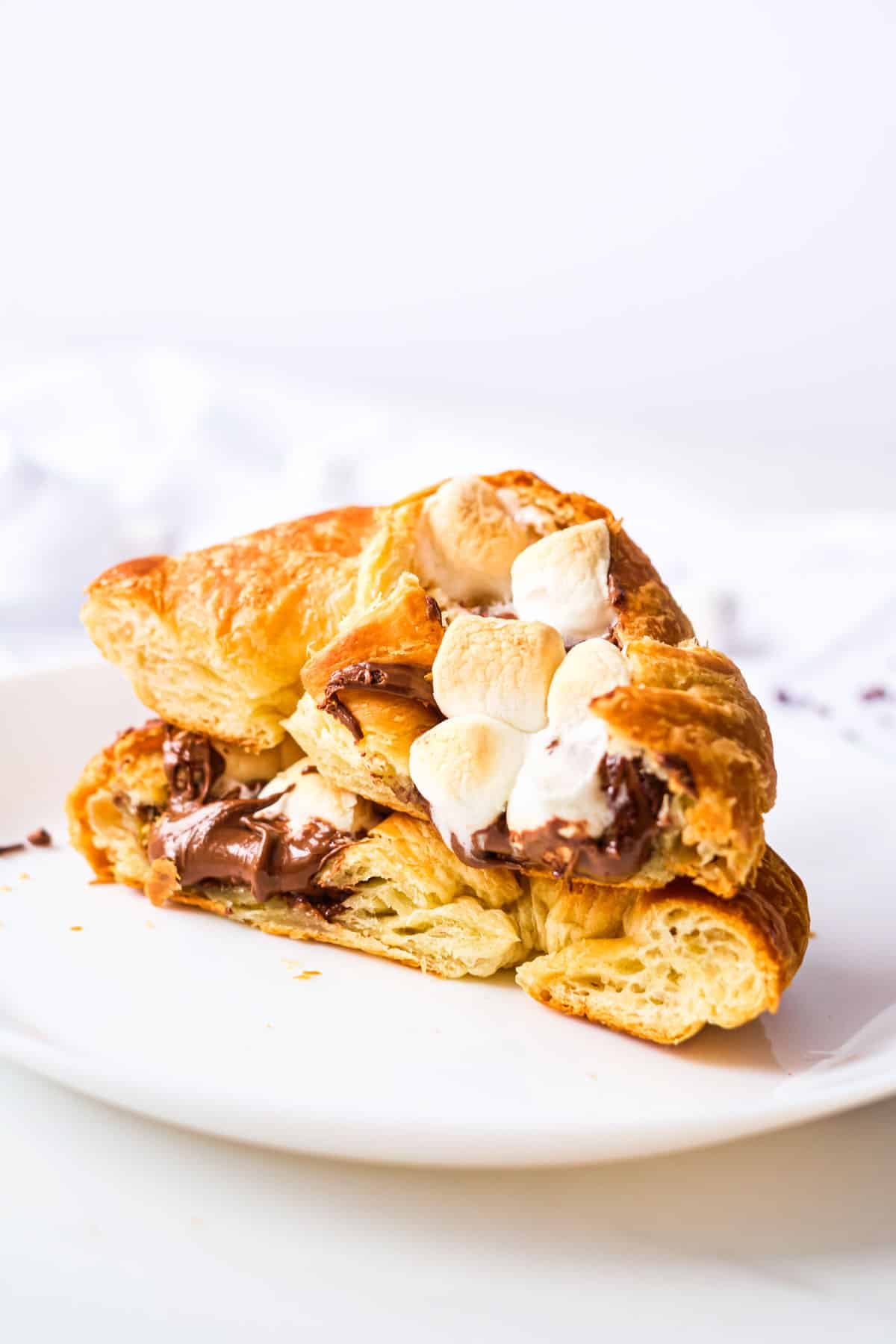 one completed stuffed croissant breakfast boat cut on half and served on a white plate