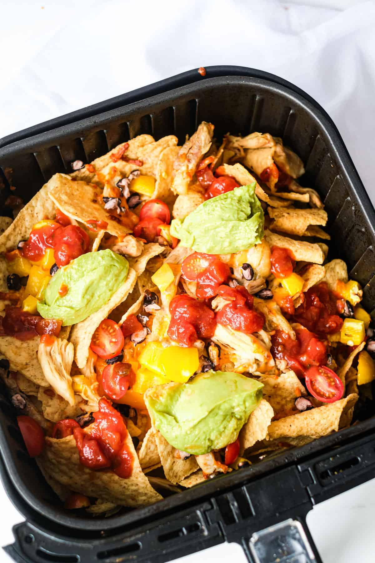 An air fryer basket full of Air Fryer Chicken Nachos with guacamole, salsa and toppings