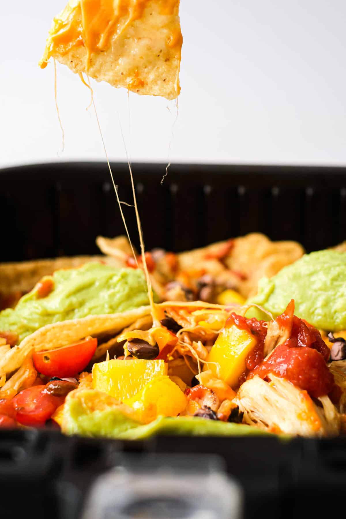 Close up of Air Fryer Nachos with topping with a cron chip being pulled out