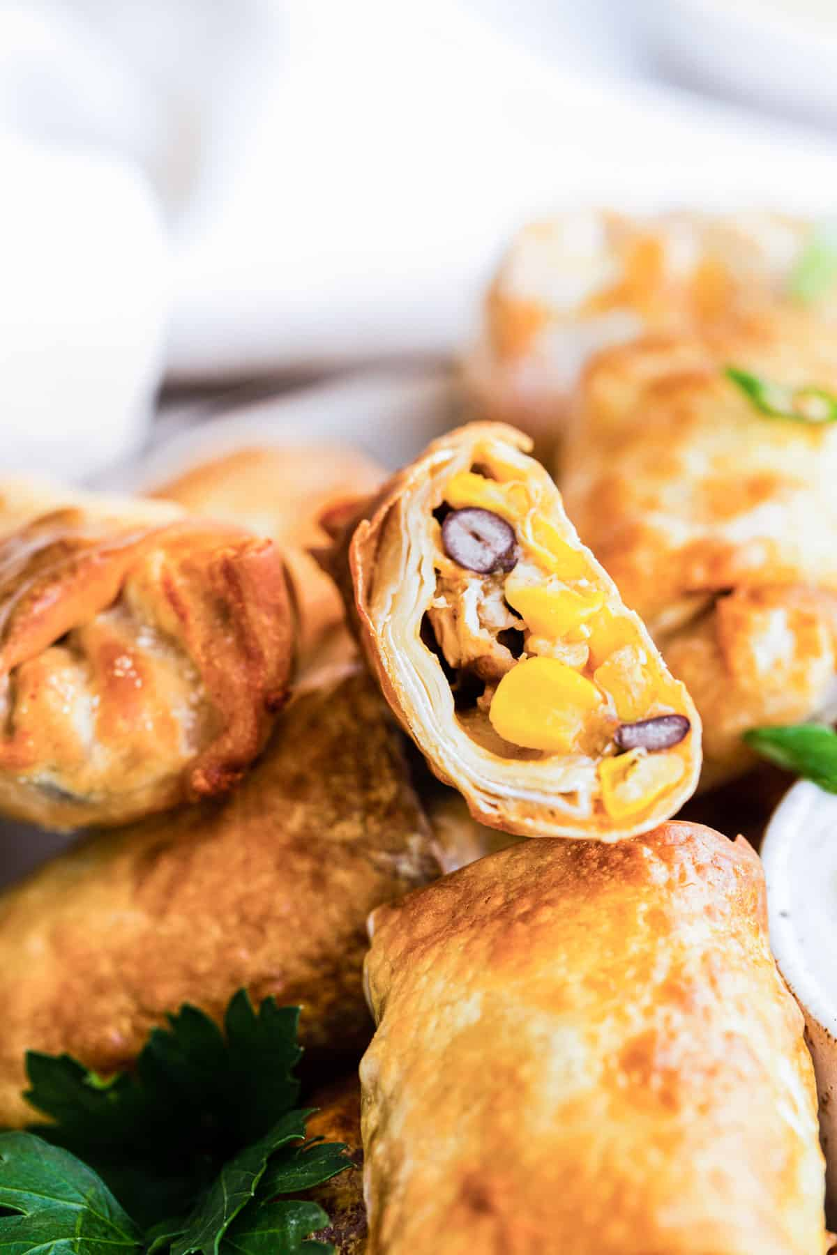 close up of chicken egg rolls with one cut up