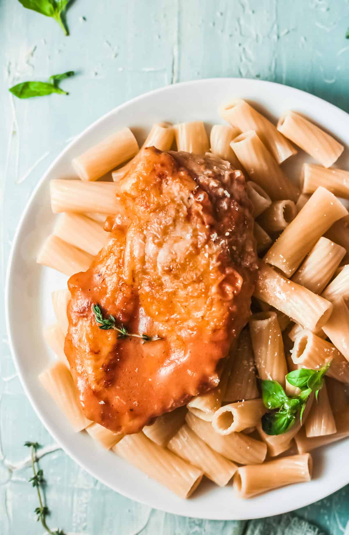 close up view of the completed cajun chicken recipe served over pasta on a white plate