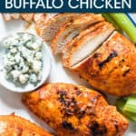 A SLICED BUFFALO CHICKEN BREAST ON A PLATE WITH CELERY AND BLUE CHEESE ON THE SIDE