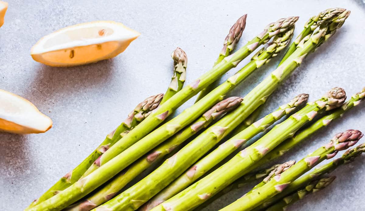 fresh asparagus and lemon wedges on a countertop