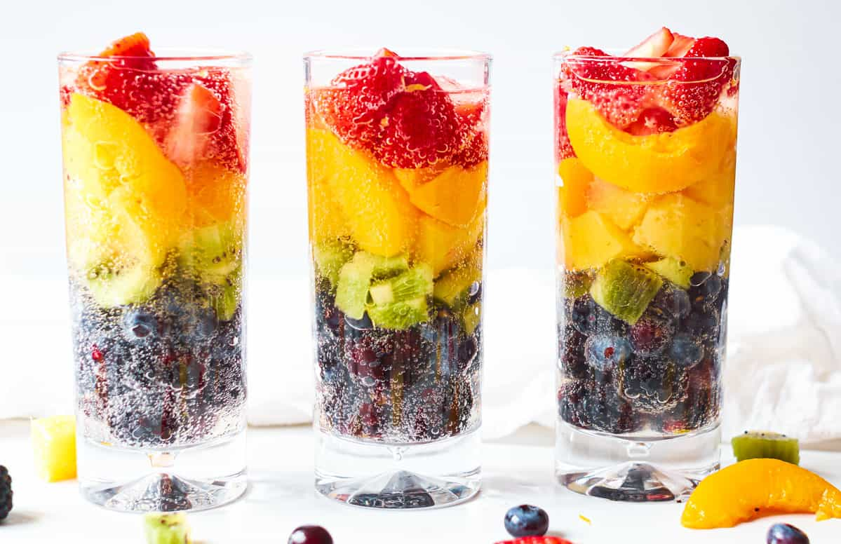 horizontal image of 3 rainbow spritzer with fruit on a table