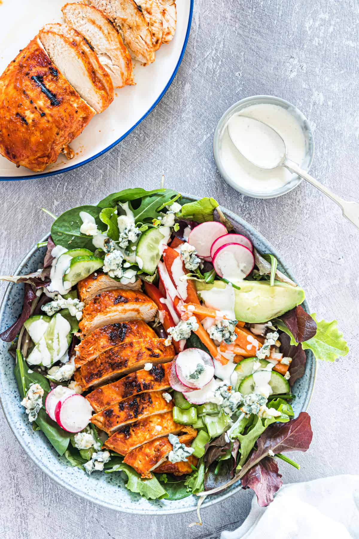 the finished buffalo chicken salad next to a plate of sliced grilled buffalo chicken and a cup of ranch dressing