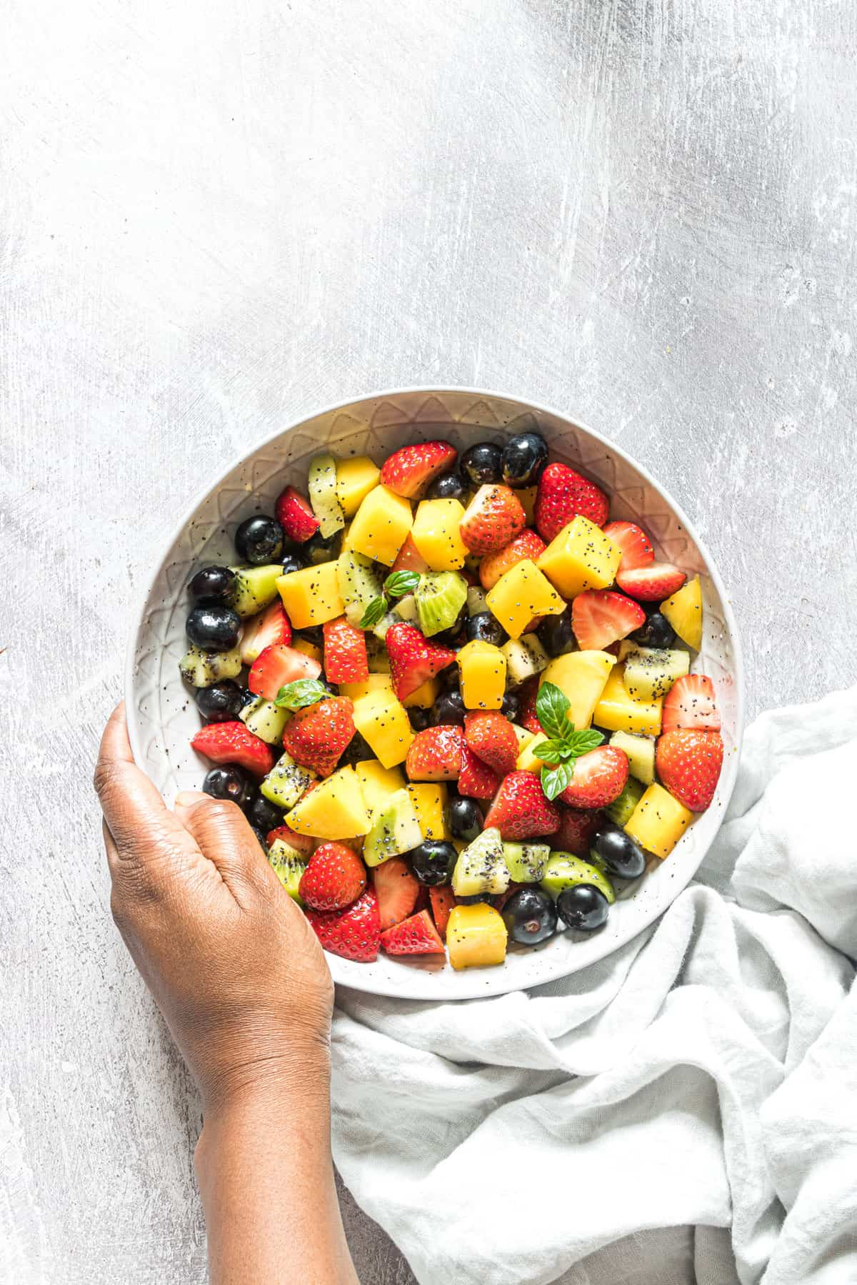 a hand holding a bowl filled with the finished fruit salad